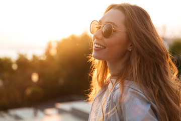 Close up image of happy brunette woman in sunglasses