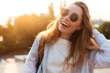 Close up picture of laughing brunette woman in sunglasses