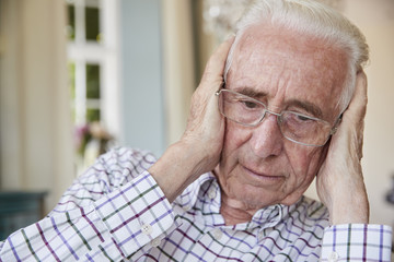 Worried senior man at home holding his head, close up
