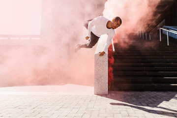 Man practicing parkour and free running with smoke grenade