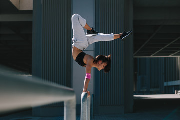 Woman doing handstand on railing outdoors