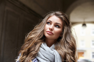 Pretty girl wearing her long voluminous hair loose standing outdoors and looking upwards with serious worried expression on her cute face. Human facial expressions, emotions, feelings and reaction