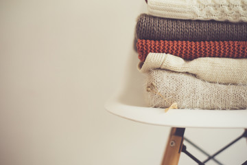 a stack of knitted warm cozy clothes, on a chair by the white wall. autumn concept.