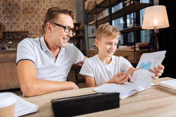 Pleasant boy describing charts to his father