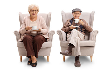 Seniors seated in armchairs drinking tea