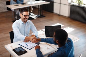Two men handshake in the office