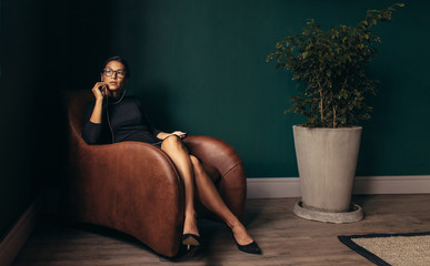 Young businesswoman sitting in armchair and talking on phone