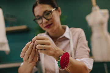Female dressmaker putting thread into needle