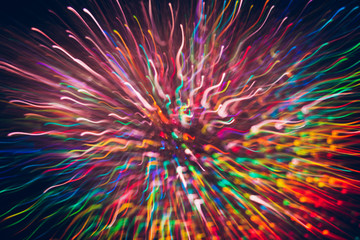 Abstract background of colorful lines in motion on black. Bokeh of defocused curves, blurred rainbow neon leds, festive backdrop of holidays and celebrations, fireworks and salute