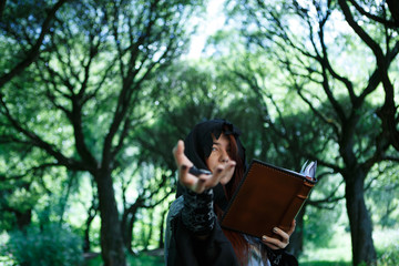 Picture of witch with outstretched hand and book