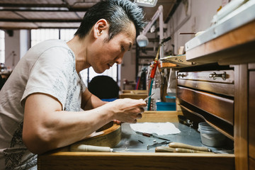 Male jeweller inspecting metal at workbench