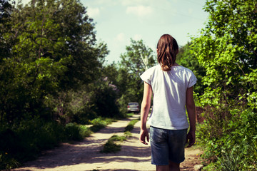 Rear view of teenage girl strolling along rural dirt track