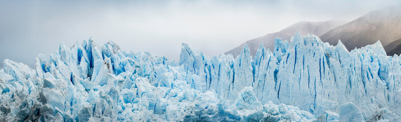 Blue iceberg against mountains