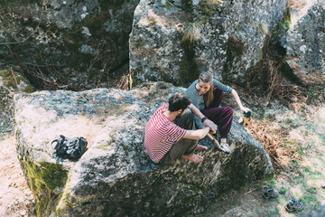 High angle view of two bouldering friends sitting on boulder, Lombardy, Italy