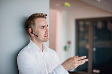 Businessman leaning against office wall talking on bluetooth earpiece