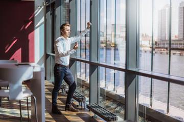 Businessman leaning against waterfront office window talking on bluetooth earpiece