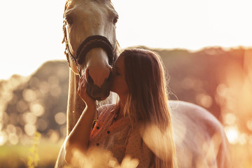 Woman kissing her horse at sunset, outdoors scene