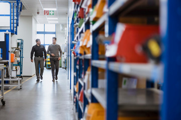 Manager and worker walking and talking in factory warehouse