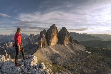 Sesto / Sexten, province of Bolzano, Dolomites, South Tyrol, Italy. A mountaineer admires the sunset at the Three Peaks of Lavaredo