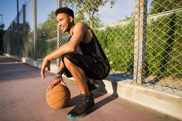 Young man on basketball court, crouching with ball