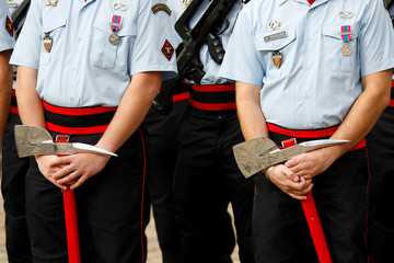 French firefighters carry axes during a ceremony to mark the 206th anniversary of Paris Fire Brigade at the Hotel des Invalides in Paris