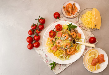 Overhead of dinner table. Pasta tagliatelle with grilled shrimps, salmon fish, gouda cheese, serving with tomato cherry, leek and basil. Ingredients around plate with tagliatelle.