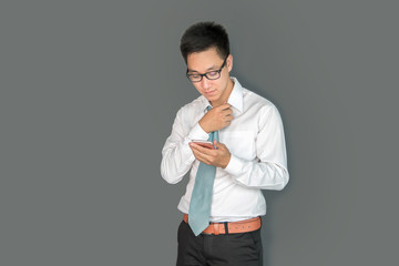 Portrait of young man holding smart phone ,looking screen with irritated expression,made a mistake, or annoyed by texts,Gray wall background