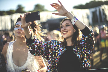 Young smiling woman at a summer music festival wearing multi-coloured sequinned jacket, taking picture with smartphone.