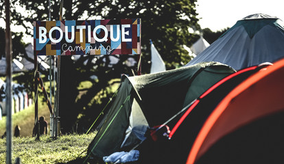Tents on grass in a camping area at an outdoor music festival in summer.  Sign reading Boutique Camping. Glamping.