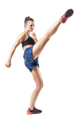 Stopped action motion of tough woman kickboxing fighter doing high kick. Full body length portrait isolated on white studio background.