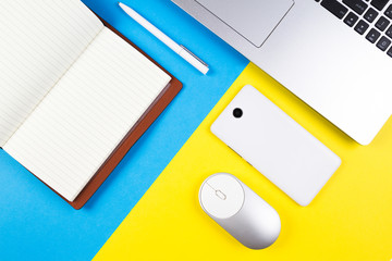 Top view of laptop, computer mouse, mobile phone, open paper notebook and pen on blue and yellow color background