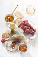 molded cheeses, fruit and snacks on a white wooden board, vertical