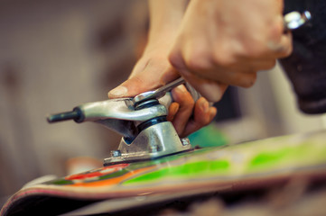 Young man in carpentry workshop fixing wheel on his skateboard