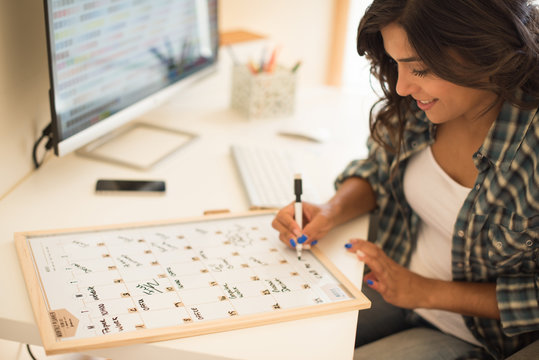 Woman on computer desk writing on a calendar