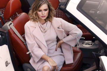 Fashion portrait of young woman in pink coat and dress outdoor