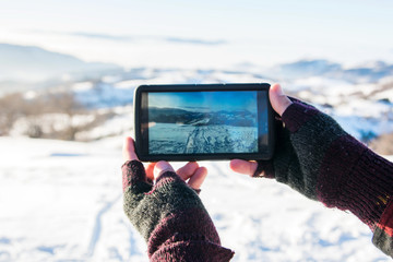 Man taking picture with a smart phone in the winter