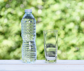 Bottle of water and glass on wood table with green nature background