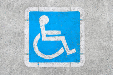 Blue disabled parking sign painted on dark asphalt in Canada in Ucluelet, Canada