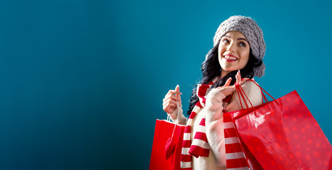 Happy young woman holding shopping bags on a solid background