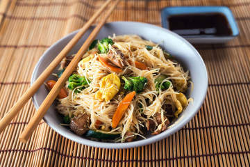 Asian rice noodles wok with chicken and vegetables