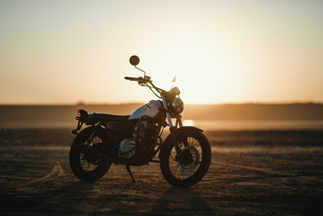 old custom beautiful cafe racer motorcycle in the desert at sunset or sunrise