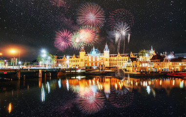 Beautiful calm night view of Amsterdam city. Colorful fireworks on the black sky background. Photo greeting card. Bokeh light effect, soft filter