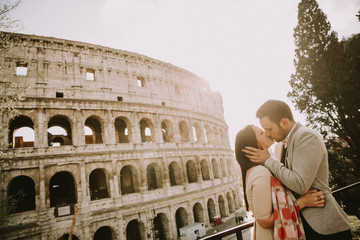 Loving couple visiting Italian famous landmarks Colosseum in Rome, Italy