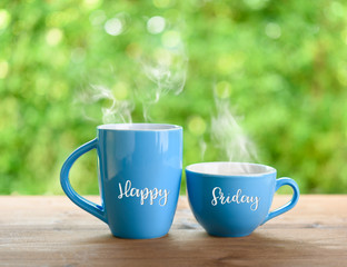 Blue Coffee cups and Happy Friday Quote on nature green  blurred  background