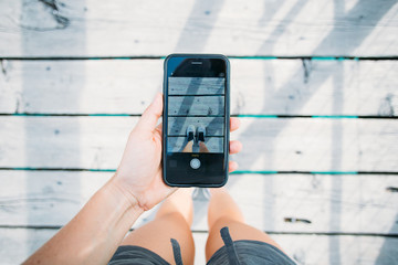 Young social media influencer with marketing ideas makes photo on smartphone of sneaker or running shoes of famous brand, standing on wooden bridge floor