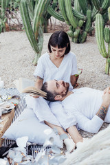 Beautiful petite brunette woman holds lover boyfriend on her lap and reads out loud from book in setting of cacti park, decorated with pillows and candles, for proposal