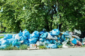 Blue garbage bags full of trash left on the street pollute the city. Garbage in the city.