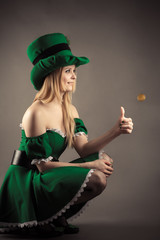 smiling blond girl in leprechaun clothes with a coin