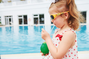 Cute little blonde at the pool and holding a child's cocktail