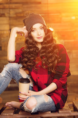 Young beautiful modern fashionable girl in a red dress and torn jeans in a cage, wearing a hat, with a smartphone and coffee on a wooden background with lights of sunlight